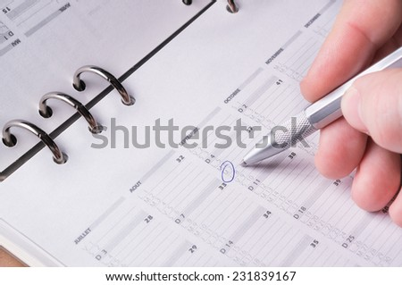 silver pen writing on open business agenda calendar - stock photo