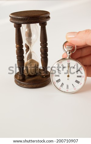 Silver pocket watch and hourglass showing the passing time - stock photo