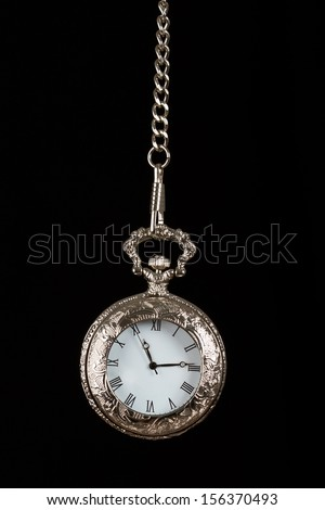 Silver pocket watch hang on chain black background - stock photo