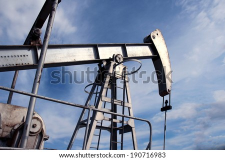 silver pump jack in crude oil field mine - stock photo