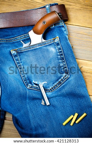 silver revolver in the back pocket of old blue jeans with a leather belt - stock photo
