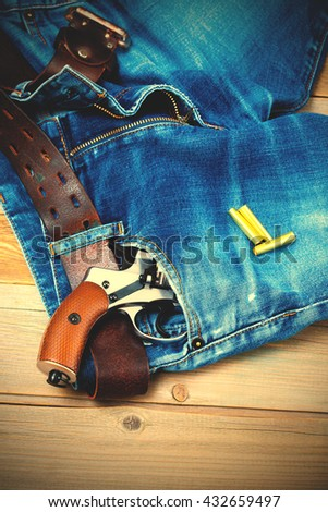 silver revolver in the pocket of blue jeans. instagram image filter retro style - stock photo