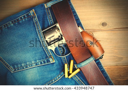 silver revolver nagant with brown handle in the pocket of old blue jeans on wooden surface. close up. instagram image filter retro style - stock photo