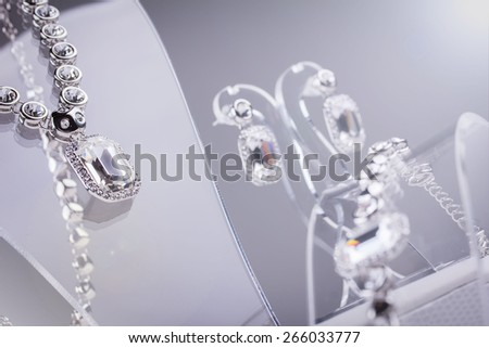 Silver set bracelet, necklace and earrings with diamond. Isolated on grey. Lens flare - stock photo