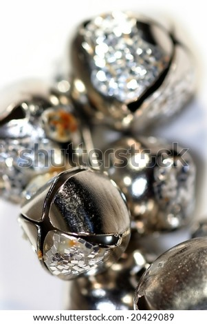 Silver shiny bells close up on white background - stock photo