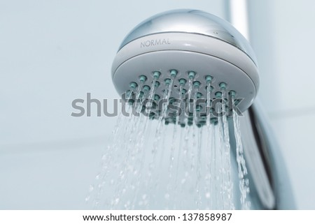 Silver shower with flowing waterin the bathroom - stock photo