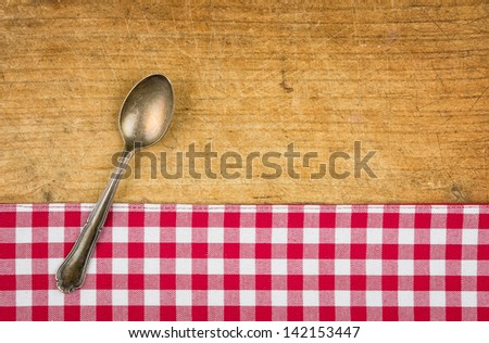 Silver spoon on a wooden board with a checkered tablecloth - stock photo