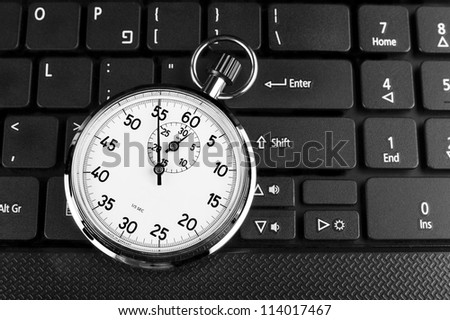 Silver stopwatch on black laptop keyboard in the background - stock photo