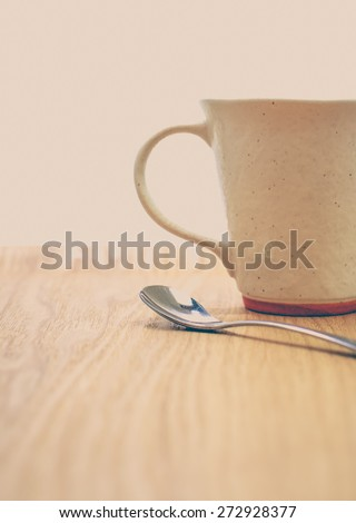 Silver tea spoon and ceramic coffee cup on wood tray - stock photo