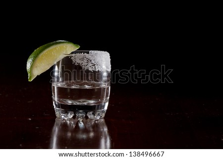 silver tequila shot served in a small glass with a lime wedge and salt on the rim - stock photo