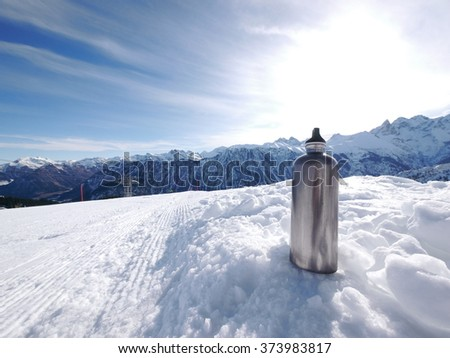 silver thermos flask slope - stock photo