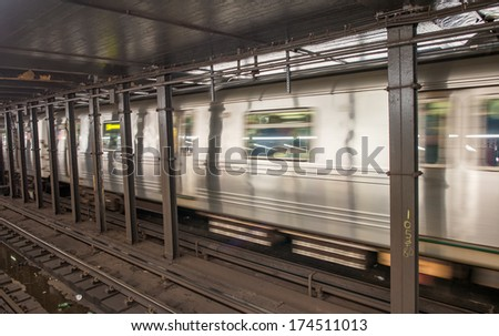Silver Train speeding up on a subway station interior. - stock photo