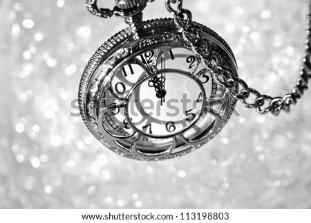 Silver vintage pocket watch with chain as viewed from above over bokeh background.  Side lighting with shadows for effect. Black and white macro with shallow dof.  Selective focus on the number 12. - stock photo
