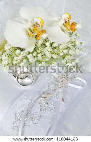 silver wedding rings with orchid bouquet on white satin pillow - stock photo