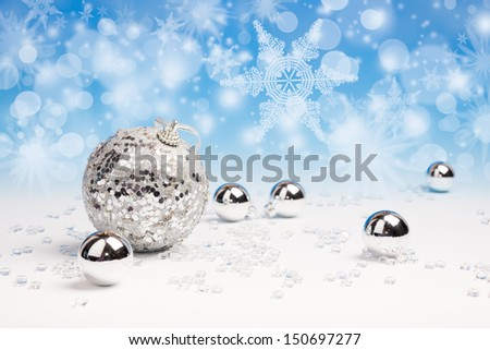 Silver Xmas baubles with abstract winter background - stock photo