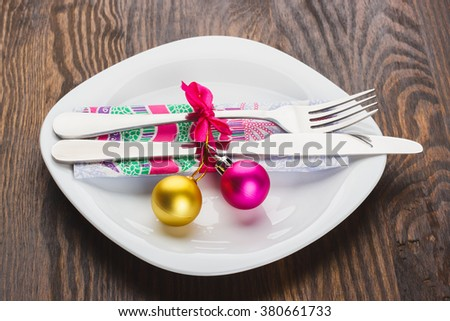 Silverware on the white plate with napkin and Christmas decorations, wooden background - stock photo