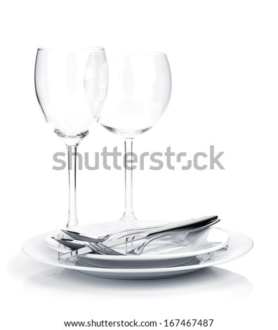 Silverware or flatware on plates and wine glasses. Isolated on white background - stock photo