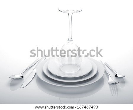 Silverware or flatware set and wine glass over plates. Isolated on white background - stock photo