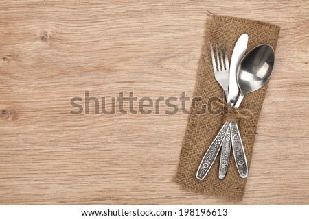 Silverware or flatware set of fork, spoon and knife on wooden table - stock photo