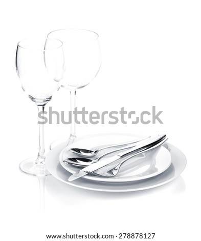 Silverware or flatware set over plates and wine glasses. Isolated on white background - stock photo
