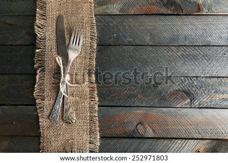 Silverware tied with rope on burlap cloth and wooden planks background - stock photo