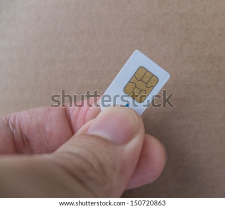 Sim card In a hand isolated on brown paper background - stock photo