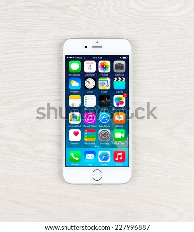 SIMFEROPOL, RUSSIA - NOVEMBER 03, 2014: Apple iPhone 6 over table displaying iOS 8.1 homescreen. iOS 8 is the eighth major release of the iOS mobile operating system designed by Apple Inc. - stock photo