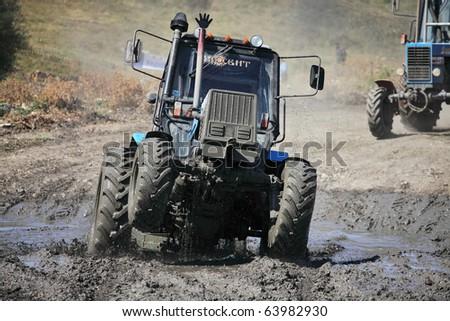 SIMFEROPOL, UKRAINE - SEPT 4: International Tractor Racing was held in the vicinity of Simferopol town at Crimea Peninsula, Ukraine - September 4, 2010. Tractor driver - Anatoliy Bobrovskiy - stock photo
