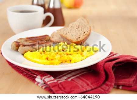Simple and Delicious Breakfast of Mini Bratwurst Sausages, Eggs Scrambled with Cheese, Toast, and Black Coffee - stock photo