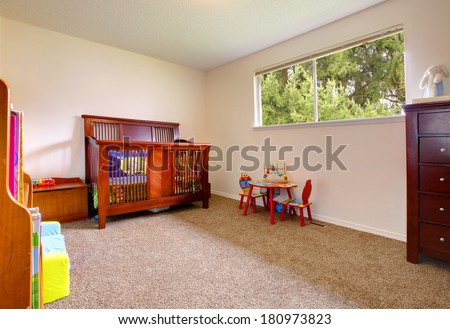 Simple baby room with cherry wood crib and toys - stock photo