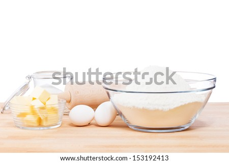 simple baking tools and ingredients on a wooden table and white background - stock photo
