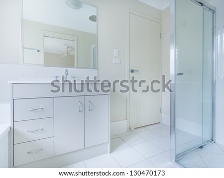 Simple bathroom with sink, mirror and shower - stock photo