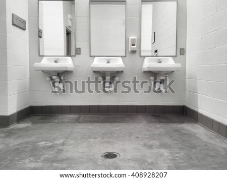 Simple but clean public washroom, row of sinks and mirrors, grungy faded-color mobile shot - stock photo