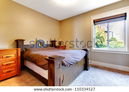 Simple classic new bedroom with nice bed and dresser with beige walls. - stock photo