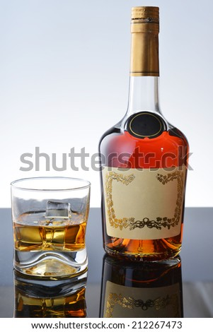 Simple composition of glass and bottle whiskey. - stock photo
