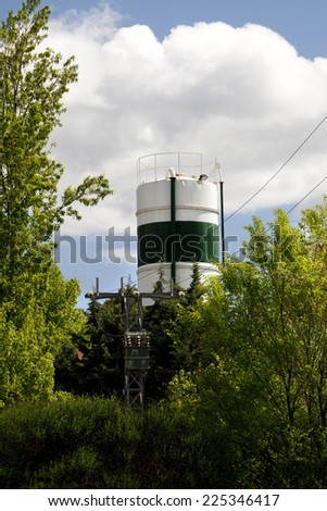 Simple composition with a big tank surrounded by trees in a forest. Tank in a forest - stock photo