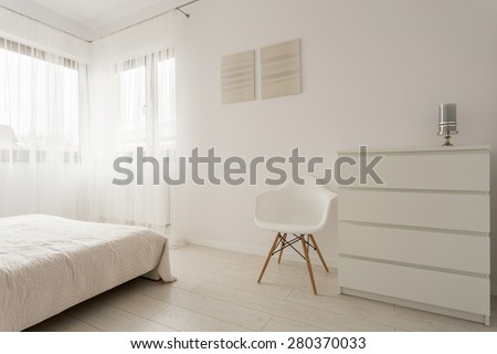 Simple exclusive white bedroom with wooden parquet  - stock photo