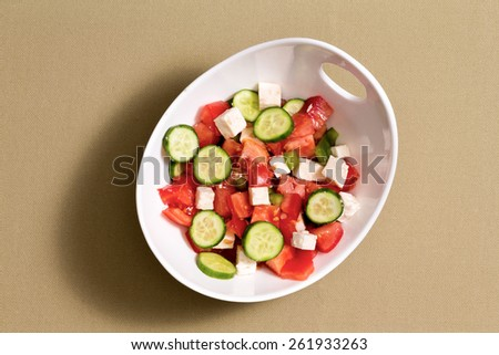 Simple fresh salad with feta cheese, cucumbers, ripe red tomato and green bell pepper served on a clean beige cotton cloth in sunshine.shadow - stock photo