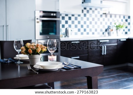 Simple home table setting with flowers, glasses and cutlery in the kitchen interior. - stock photo