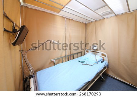 Simple interior hospital room with a bed, a TV and electroencephalograph - stock photo