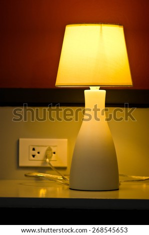 simple lamp with yellow shade on a wooden desk casting a shadow onto a plain wall - stock photo