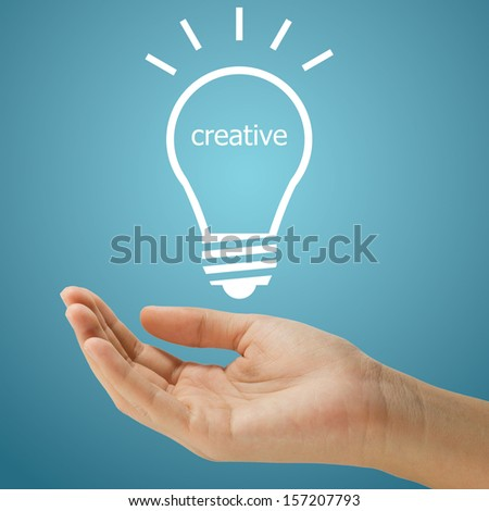 simple lightbulb with creative word floating on women hand on blue background - stock photo