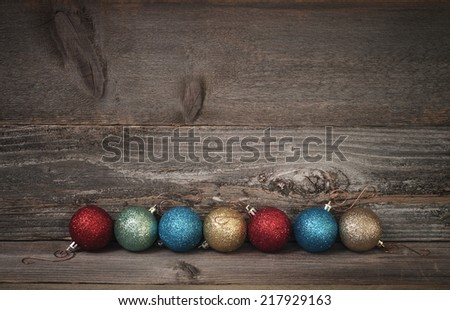 Simple Line of Glitter Christmas Ornaments on Rustic Barn Wood Board Floor and Wall with room or space for copy, text, your words.  Dark Vignette horizontal - stock photo