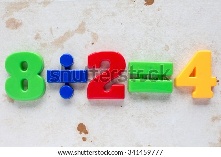 Simple math division formula on old paper background - stock photo