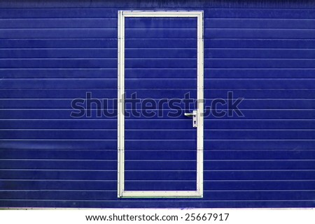 simple metal door in blue wall - stock photo