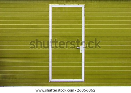 simple metal door in yellow wall - stock photo