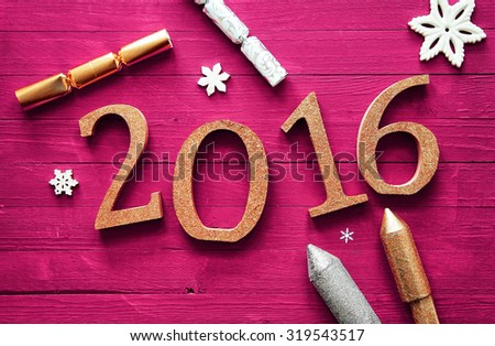 Simple 2016 New Year Celebration Design on a Wooden Magenta Table with Firecrackers and Snowflakes. - stock photo