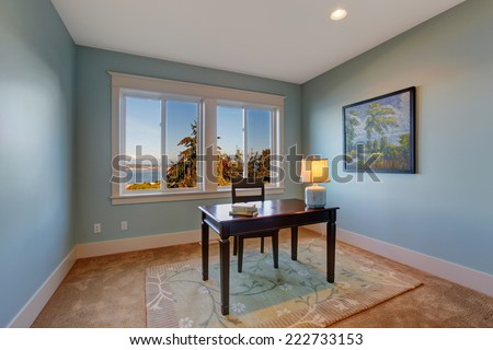Simple office room in light blue color and bay view. Dark brown desk with chair - stock photo
