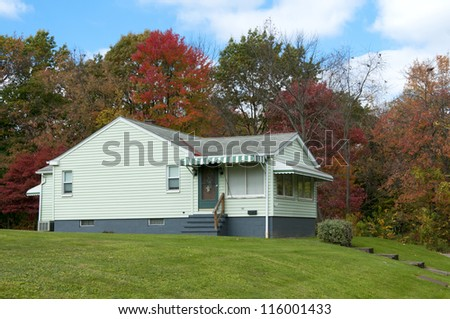Simple one story home  with awnings and autumn foliage - stock photo