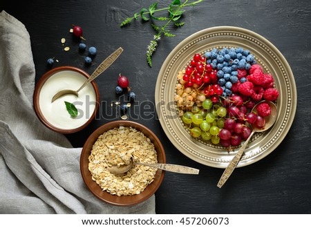 Simple rustic breakfast with various  garden berries, yogurt and oat granola, dark moody background, view from above - stock photo